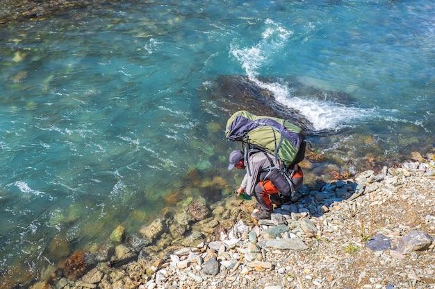 川から大きなバックパックの飲料水を持つ観光客の男。川の汚染されていない水をきれいにします。山川から水を飲む。