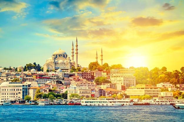Туристические кораблики в бухте золотой рог в стамбуле и вид на мечеть сулеймание с районом султанахмет на фоне красивого заката.
