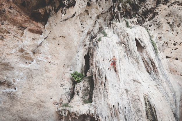 Tourists are climbing cliffs at railay bay, krabi.