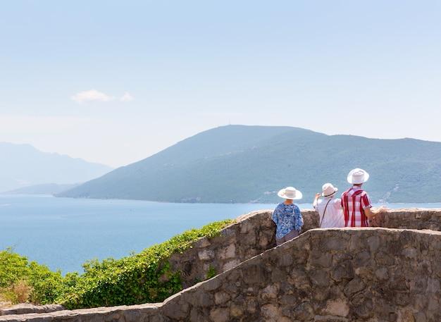 관광객들은 산에서 바다의 경치를 즐기고 있습니다.