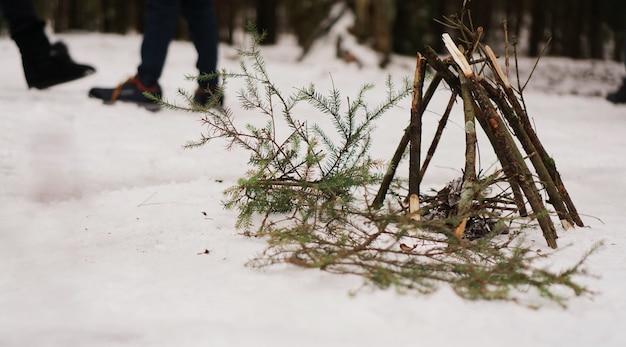 Туристы на привале. подготовка к разжиганию костра из еловых веток. зимний лес