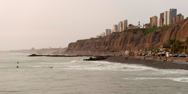Tourists on the beach with a city in the background, miraflores district, lima province, peru