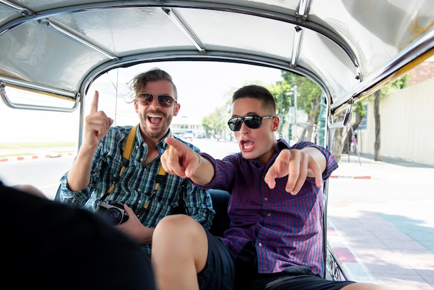 Tourists being excited and having fun on tuk tuk taxi in thailand