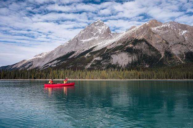 Туристы плывут на каноэ на остров духов с канадскими скалистыми горами на озере малинье в национальном парке джаспер, ab, канада
