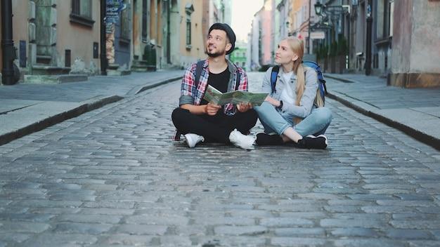 Туристы сидят на тротуаре с картой и любуются историческими окрестностями. они взволнованы и улыбнулись.