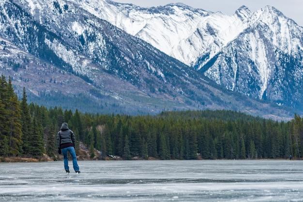 겨울 밴프 국립 공원에서 존슨 호수 얼어 붙은 수면에서 아이스 스케이팅을하는 관광객