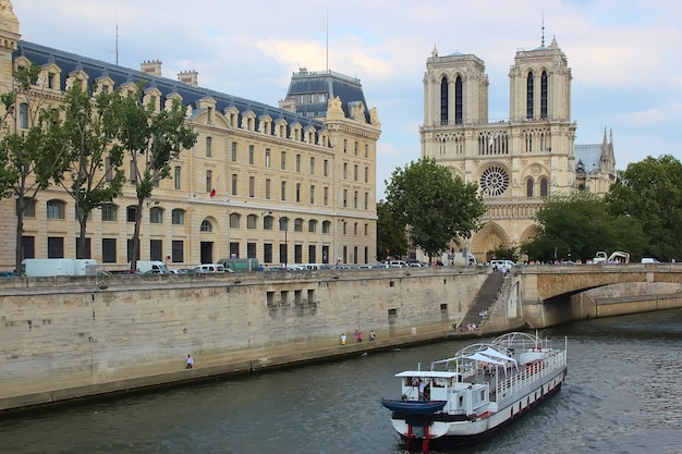 Tourists enjoy a boat trip on seine river near notre dame cathedral