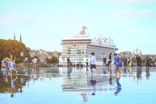 Tourists enjoy walking on bordeaux water mirorr with famous dutch cruise ship on the back