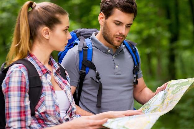 Туристы изучают карту. задумчивая молодая пара с рюкзаками изучает карту, стоя на природе