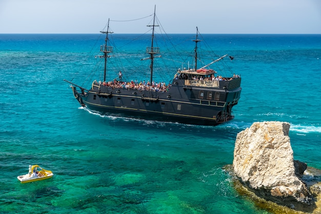 Tourists float on a galleon near the coast