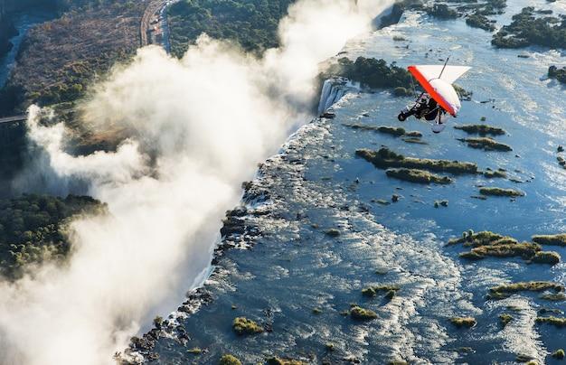 観光客はトライクでビクトリアの滝の上を飛ぶ。アフリカ。ザンビア。ビクトリア滝。