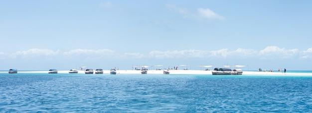 晴れた日に小さな熱帯の島に集まる観光客