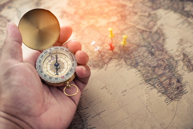 Tourists hold a compass and locate a place on a world map.
