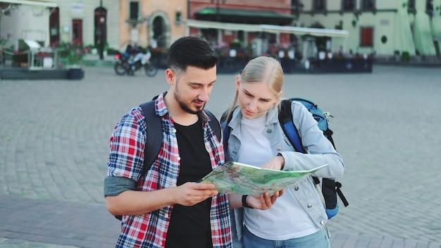 Туристы держат карту и ищут какое-то место на городской площади. идут осматривать достопримечательности.