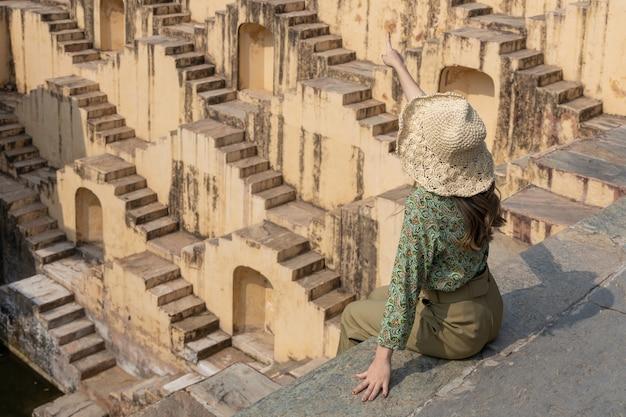 Туристы исследуют древний индийский степной колодец, лестничную архитектуру в абханери баори степ в джайпуре, раджастхан, индия.