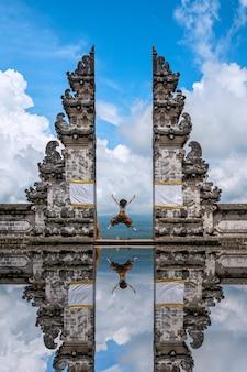 Туристы прыгают в храм лемпуянг, бали, индонезия