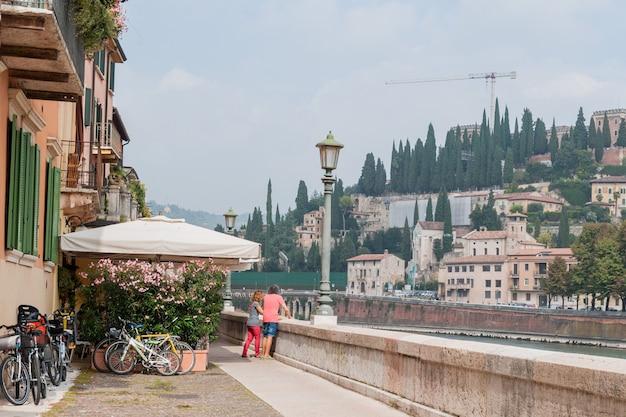 観光客はルンガディからカステルサンピエトロを見て、観光客はイタリア、ヴェローナのルンガディジェトゥリオドナテッリからカステルサンピエトロを見て