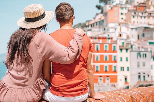 Tourists looking at scenic view of riomaggiore, cinque terre, liguria, italy Premium Photo