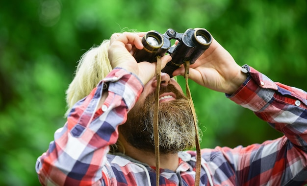 쌍안경을 가진 관광객 남자 숲을 따라 뭔가 찾고 있습니다. 숲에서 쌍안경 망원경을 가진 남자입니다. 여행 개념입니다. 먼 미래를 바라보고 있습니다. 취미와 휴식.