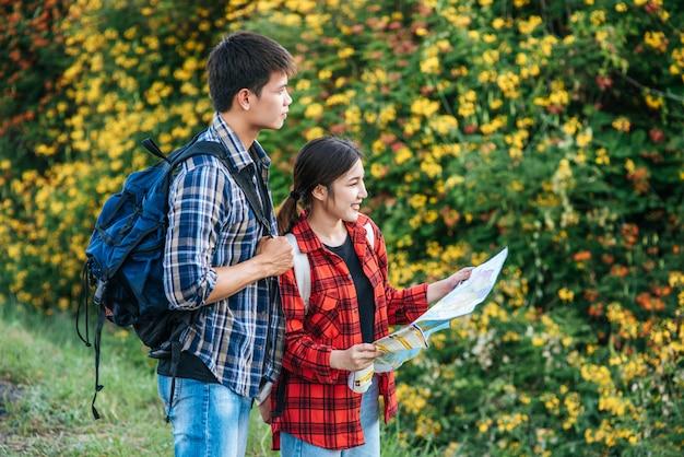 Туристы мужчины и женщины смотрят на карту возле цветников.