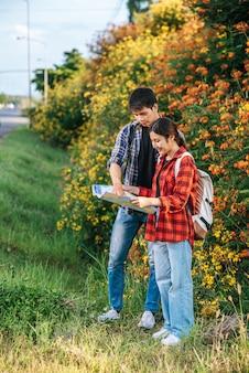 観光客の男性と女性は花畑の近くの地図を見ます。