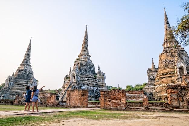 観光客の母と娘の写真撮影古代遺跡とワットプラシーサンペット寺院の塔タイ、アユタヤ県のプラナコンシアユタヤ歴史公園の有名なアトラクション