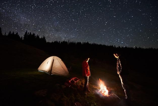キャンプファイヤーと夜の星空の下でテントの近くの観光客