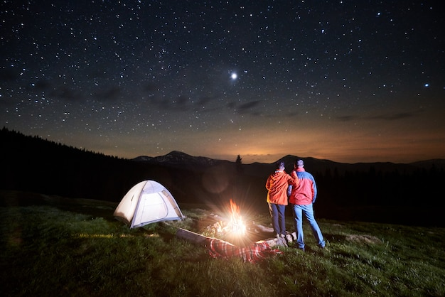 Tourists near campfire and tent under night starry sky
