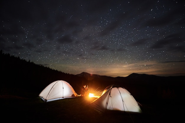 Tourists near campfire and tents under night starry sky