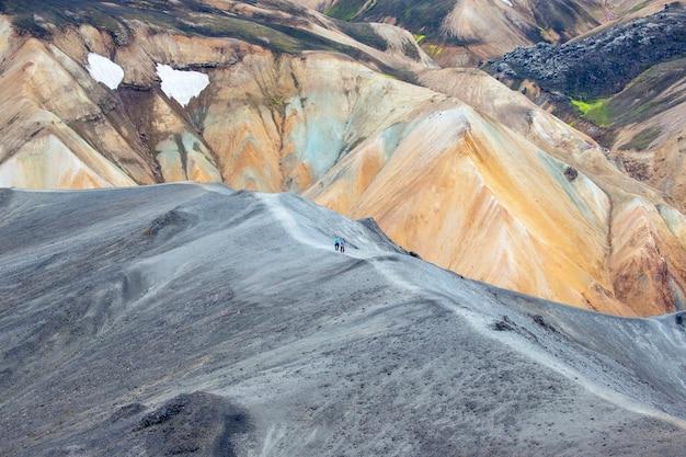 관광객은 landmannalaugar의 산길 경사면을 통과합니다.