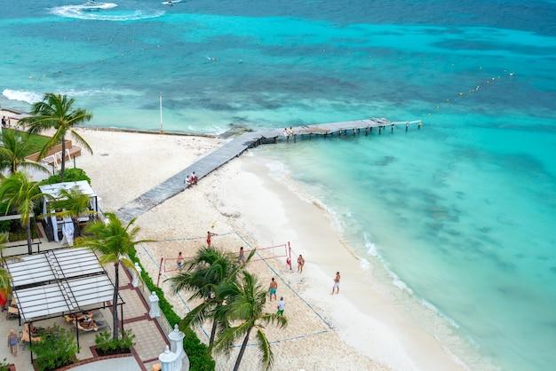 Туристы играют в волейбол на пляже в роскошном отеле в канкуне, мексика