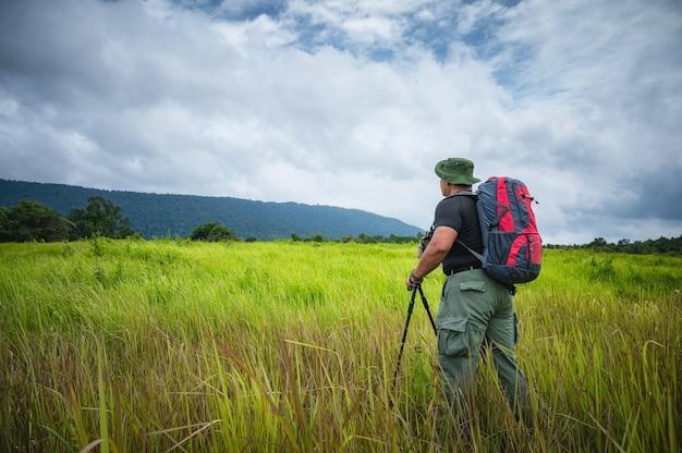 관광객들은 열대 우림의 초원에서 새와 야생 동물을 찾기 위해 쌍안경을 사용할 준비를 합니다. 태국 카오야이 국립공원. 새, 코뿔새, 원숭이 투어. 생태 관광 개념 사진입니다.