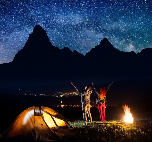 Tourists raised their hands up under stars near campfire and tent