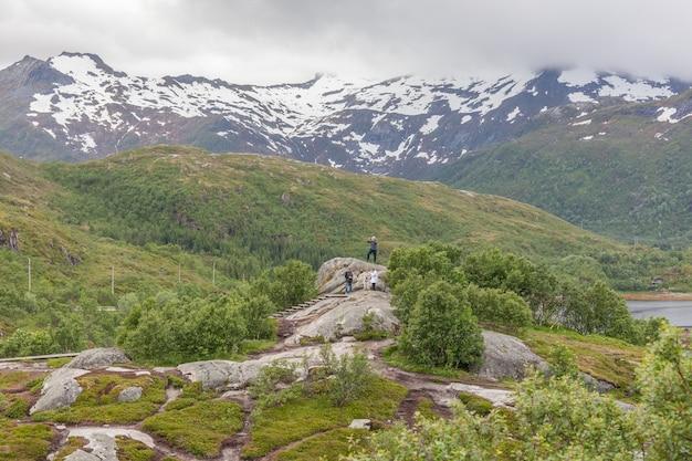 Туристы отдыхают на скале и наслаждаются видом на норвежские фьорды.