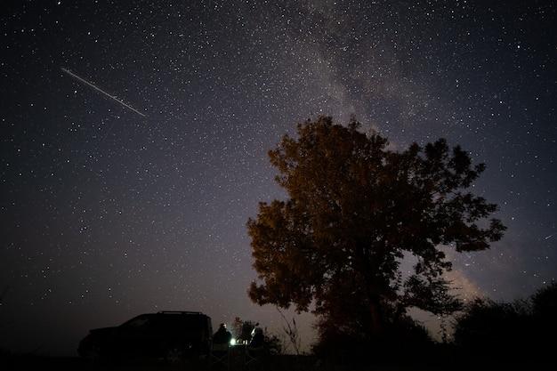 Туристы отдыхают в ночном путешествии под одиноким деревом и звездным небом с млечным путем. их внедорожник припаркован поблизости.