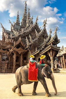 Tourists ride elephant around the sanctuary of truth in pattaya in thailand