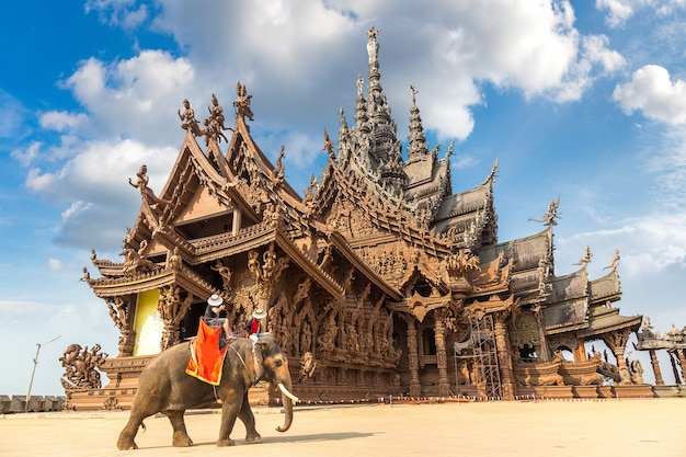 Tourists ride elephant around the sanctuary of truth in pattaya, thailand
