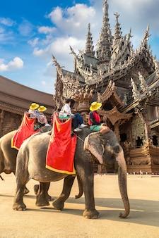 관광객들은 파타야 진리의 성전 주변에서 코끼리를 타고