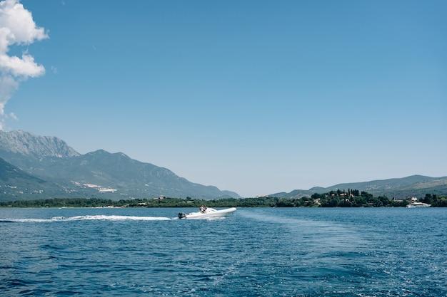 観光客はモンテネグロの山々に対して海の白いスポーツボートに乗る