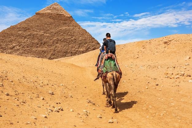 기자 카프레의 피라미드 근처에서 낙타를 타고 있는 관광객들.