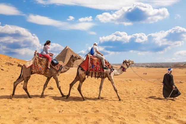 ギザのピラミッドの近くでラクダに乗る観光客。