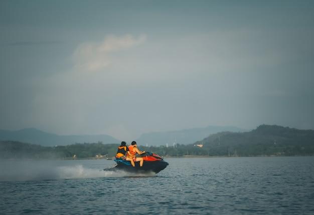 Туристы катаются на водных мотоциклах. высокая скорость в море или реке с разбрызгиванием воды.