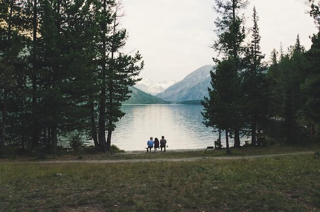 관광객들은 알파인 호수 기슭의 벤치에 앉아 저녁 빛의 아름다운 전망을 감상합니다.