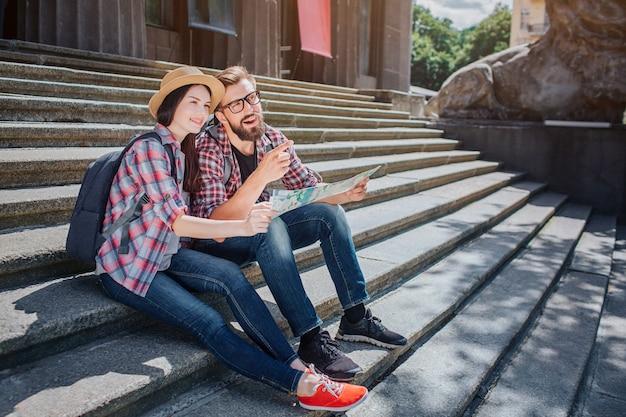 관광객들은 계단에 앉아 기대합니다. 젊은 남자 포인트. 그들은 웃어요. 사람들은 함께지도를 가지고 있습니다. 밖은 맑습니다.