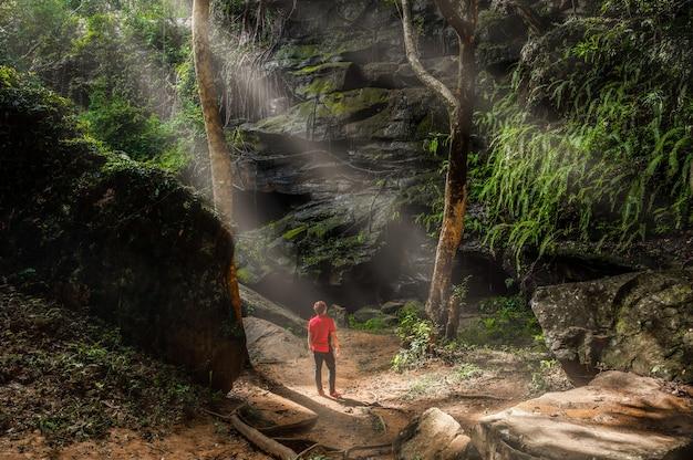 관광객들은 태국 콘캔의 푸위앙 국립공원 내 최고의 폭포인 탓파 폭포의 열대 우림에 빛줄기가 비치는 큰 바위 앞에 서 있습니다.