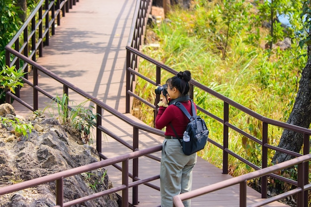Tourists stand take photo to travel at on the nature trail at chae son national park lampang