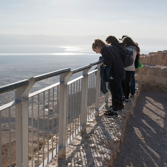 Tourists standing on terrace of fort, masada, judean desert, dead sea region, israel