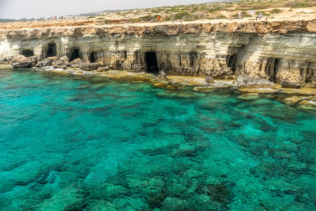 観光客は絵のように美しい海食洞の近くの海岸に沿って散歩します