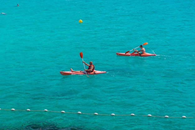 관광객들은 지중해의 인기 만에서 뗏목과 카약을 타고 수영합니다.