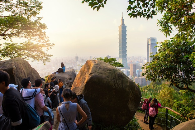 Tourists take pictures with 101 tower at sunset